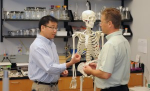 Hai Yao, the Ernest R. Norville Endowed Chair of bioengineering at Clemson University and leader of SC-TRIMH, talks with a student in his lab at MUSC. Image Credit: Grace Beahm