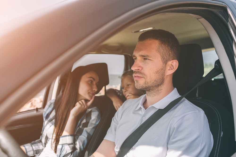man in the car with his family on vacation
