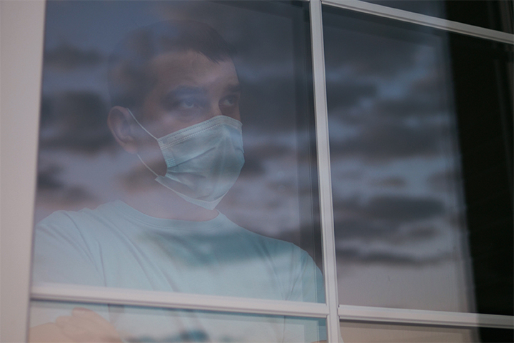 A gloomy portrait of a man wearing a protective mask looking out the window