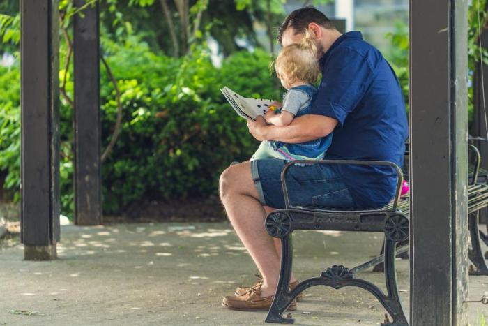 un homme fait la lecture à un bébé sur ses genoux