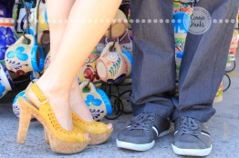 Connie Hanks Photography // ClickyChickCreates.com // engagement couple session, Rosarito, Mexico, mercado, market, colorful, turquoise, blue, gray, wood, wheel, rustic, arches, archways, kiss, sombreros, shoes, style, high heels, sneakers