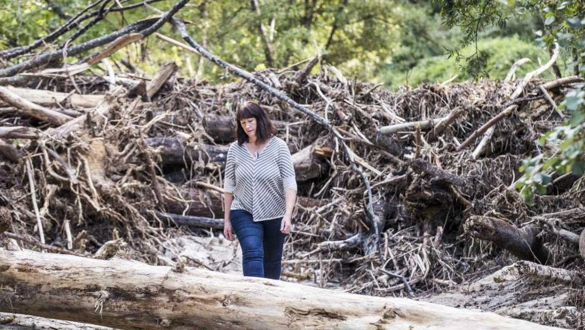 Fig. 4: Lyn Rombouts among the masses of tree waste or 'slash' that washed down onto her Motueka property after heavy rain in February 2018. In clear-fell forestry, a system favoured in New Zealand's commercial forests, entire forests are removed and restocked at the same time (Image: Braden Faster/Stuff).