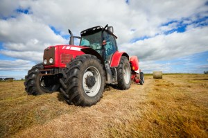 Tractor collecting hay bales in the field
