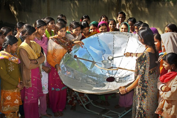 """Women learning how to use a solar cooker. Solar cookers can help to reduce deforestation and carbon production bringing cleaner air locally as well as lower carbon globally."" Climate Outreach Climate Visuals Portal"