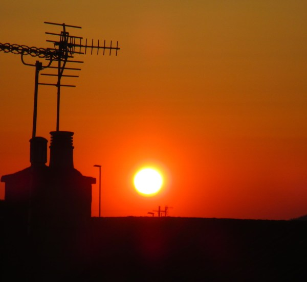 signal and purpose - showing the sun above rooftop with aerial