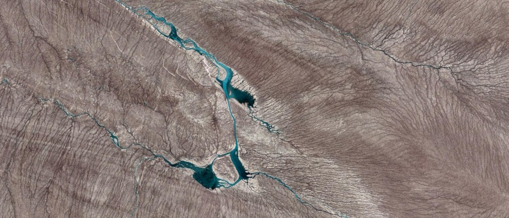 Record Greenland Melt August 2012. This image is from 35 miles inland from the edge of the ice sheet due east from a place called Point 660, which is about 18 miles ENE of Kangerlussuaq on the west coast. The ice is about 2,000 feet thick here. The dark brown color is eons of dust, melted out of the ice sheet. Most of the dust does not wash away with melt because the surface of the ice is exceeding rough.