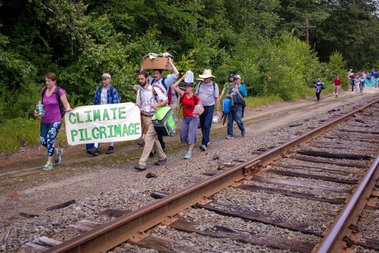 """Protesters march during a """"climate pilgrimage"""" along railroad tracks that lead to the Merrimack Station, a coal-fired power plant, in Bow on Saturday, July 15, 2017. (ELIZABETH FRANTZ / Monitor staff)"""