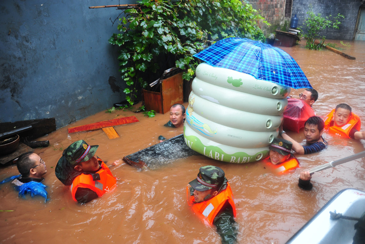 Rescuers evacuate residents carrying their possessions through the flooded streets. Getty