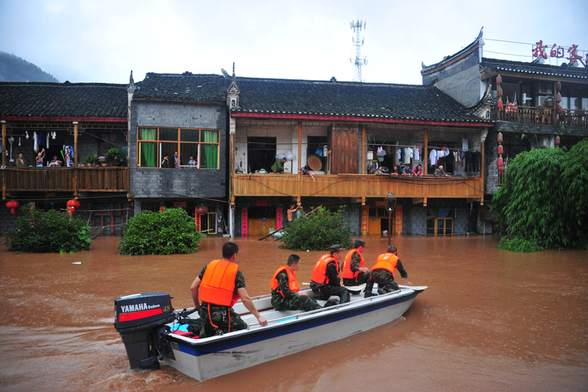 Rescuers use a boat to evacuate residents from flooded homes. Getty