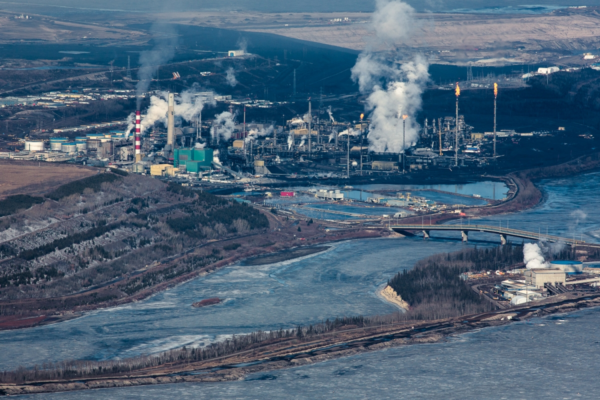 Smoke, steam, and gas flares rise from the Suncor upgrading facility. Reclamation efforts seen to the right, on what was once a tailing pond. Suncor has reclaimed only 7 per cent of their total land disturbance.
