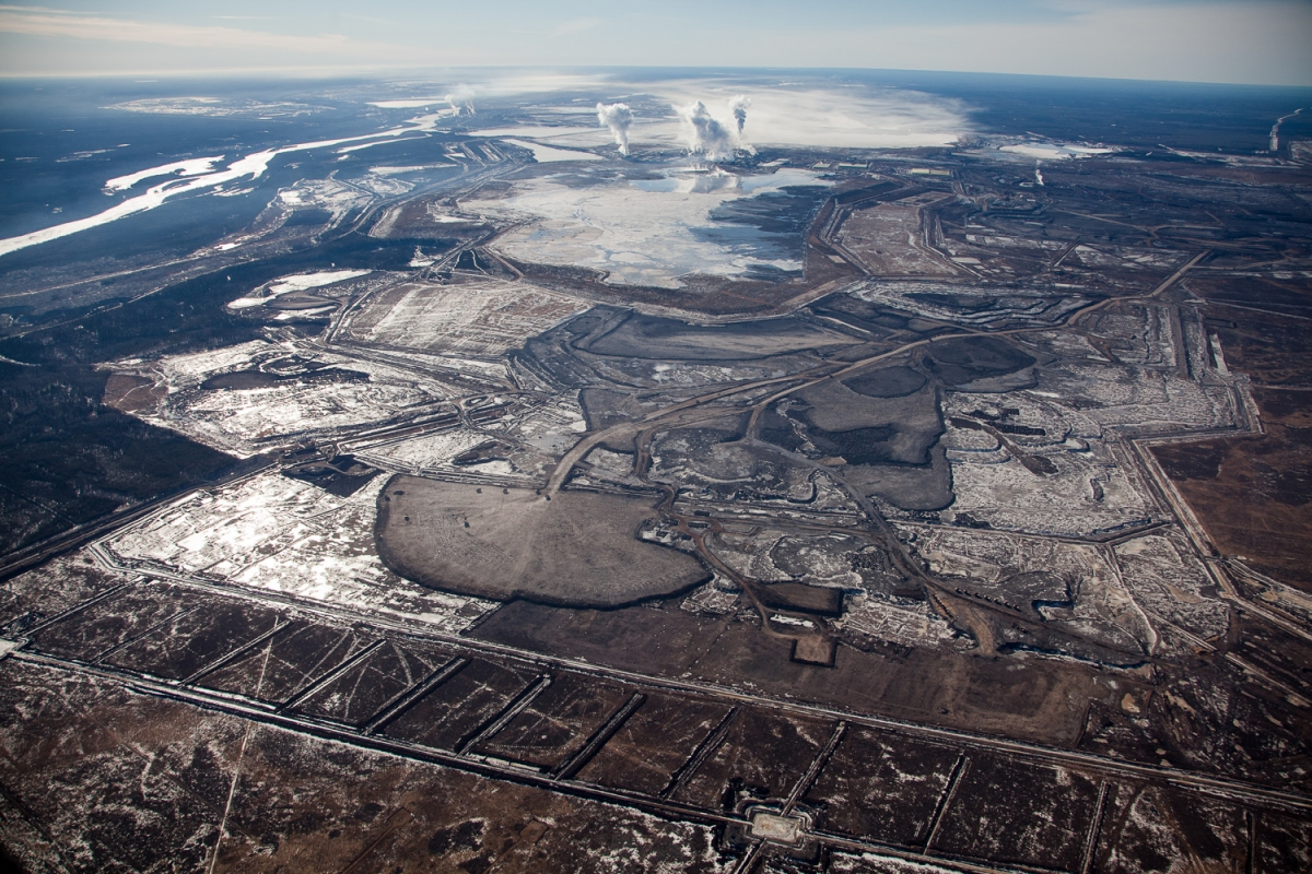 Syncrude Mildred Lake mining site. View south to upgrading facility with rising plumes of steam and smoke. Alberta, Canada.