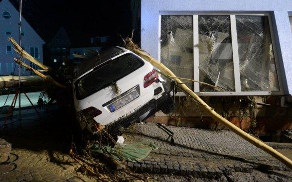 Ein Auto liegt am 30.05.2016 in Braunsbach (Baden-Württemberg) an eine Hauswand gespült. Durch heftigen Regen sind zwei kleine Bäche über die Ufer getreten, Häuser und Autos wurden beschädigt. Foto: Franziska Kraufmann/dpa +++(c) dpa - Bildfunk+++
