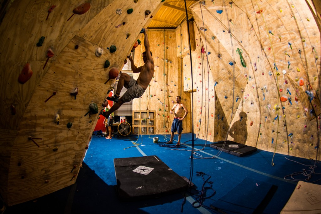 Galloway working on a boulder problem in the Cayman Climbing Gym