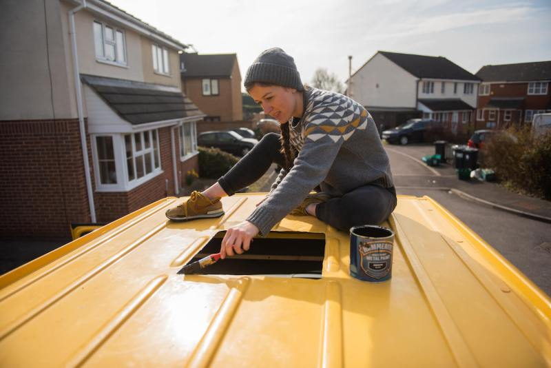 girl in geometric jumper painting Hammerite onto a Sprinter van conversion in order to install a skylight