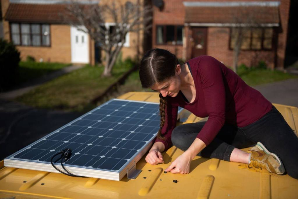girl using well nuts to install Renogy solar panels on a van conversion