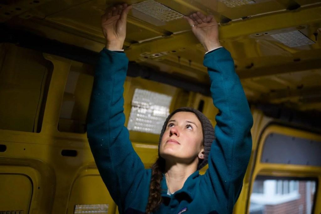 girl sticking sound deadening strips onto a Sprinter van conversion