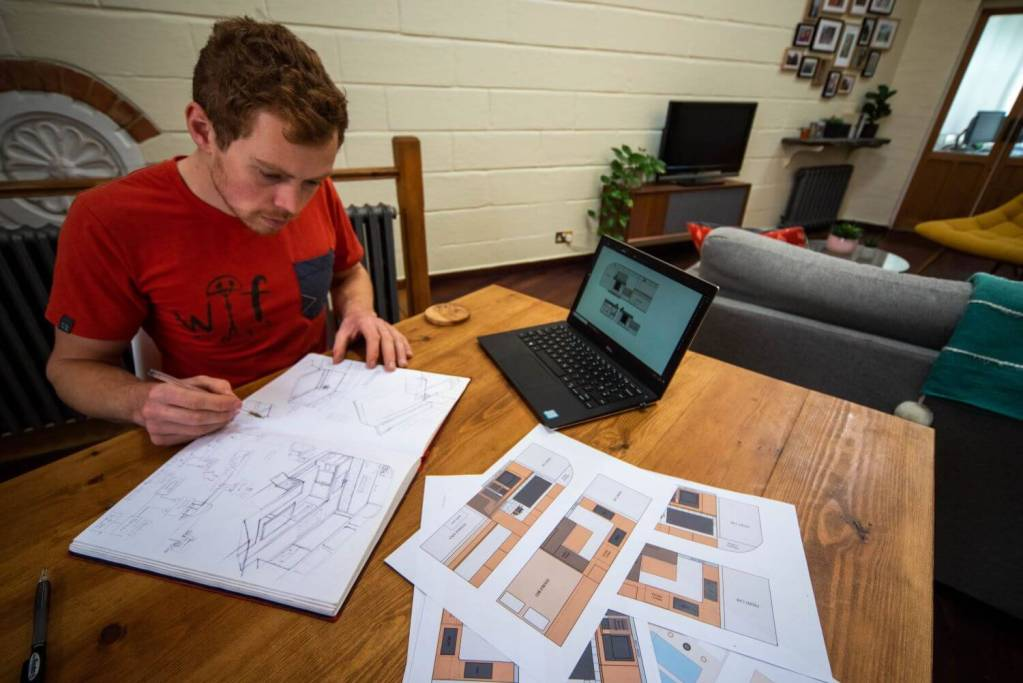 man sketching out designs and layouts for a campervan conversion