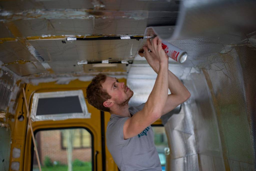 man applying ThermaWrap silver foil bubble wrap insulation to the floor of a van conversion using spray adhesive glue