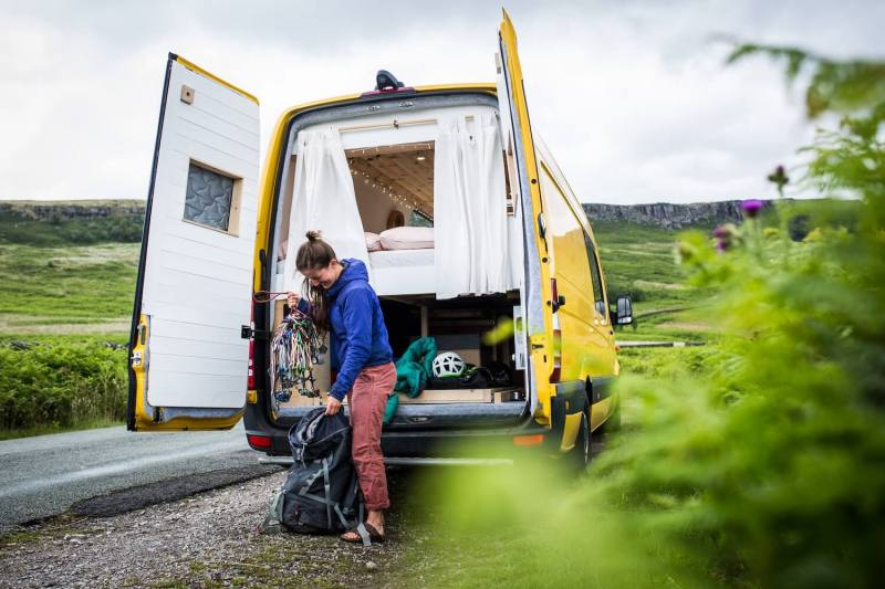 girl packing a rucksack with climbing gear outside a campervan in the peak district