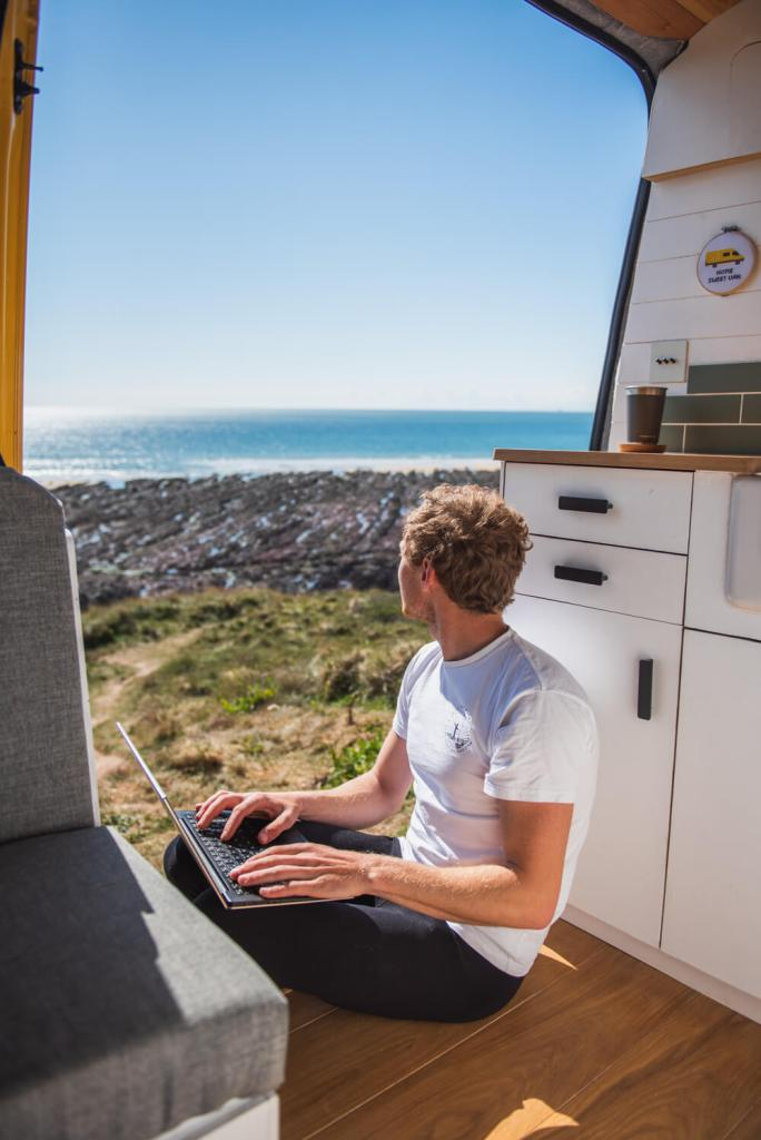 digital nomad man remote working in campervan online work with a view of the sea