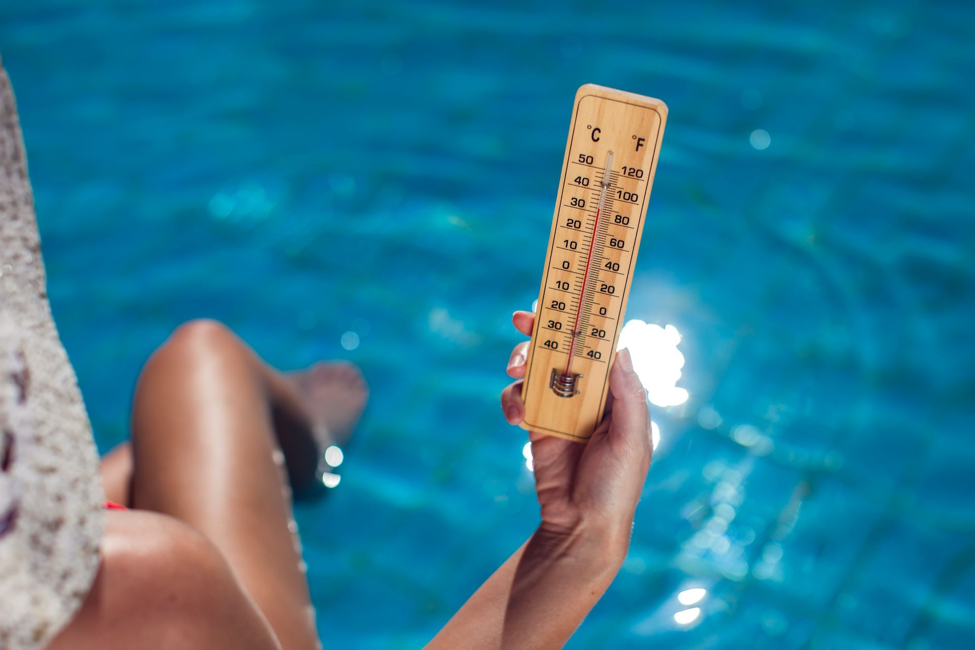 Femme montrant un thermomètre au dessus d'une eau bleue