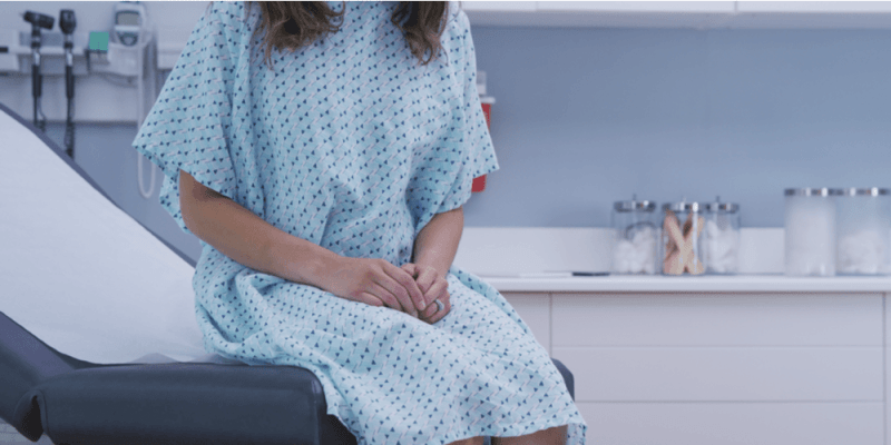 Woman in hospital gown sitting on exam table