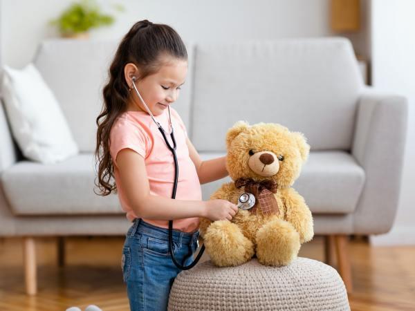 Kid Girl Playing Doctor Using Stethoscope Treating Teddy Bear Indoor