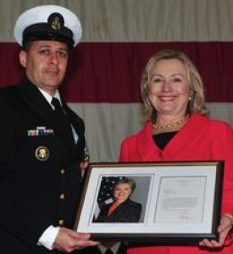 Clinton presents a letter of congratulations and signed photo to Chief Culinary Specialist Oscar Flores during his retirement ceremony aboard the USS Makin Island on April 1, 2010. (Credit: Chief Mass Communication Specialist John Lill / US Navy)