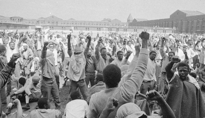 FILE — In this Sept. 1971 file photo, Inmates at the Attica Correctional Facility, in Attica, NY, raise their hands in clenched fists in a show of unity during the Attica uprising, which took the lives of 43 people. Fifty years after the Attica prison uprising, the families of slain and injured prison guards say they're still waiting for an apology from the state. (AP Photo/Bob Schutz, File)