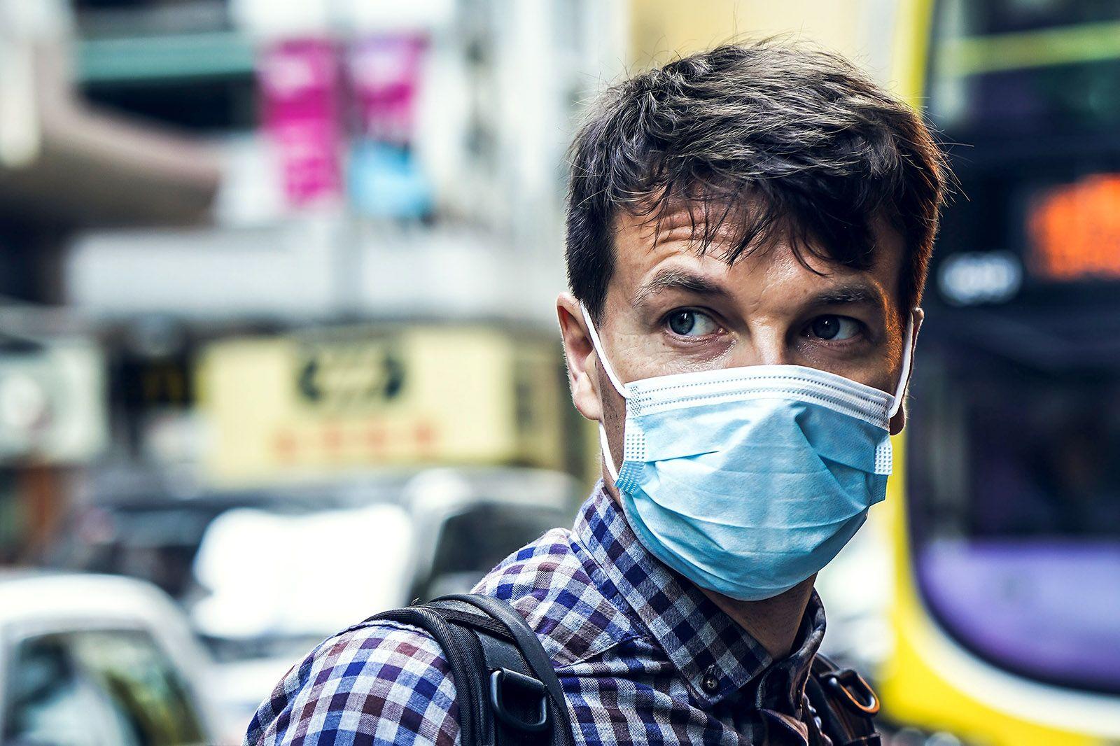 Hombre usando una mascarilla de papel en exterior