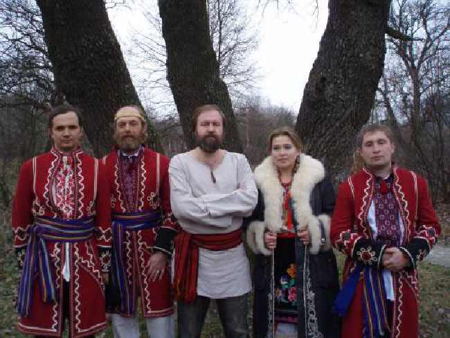 A photo of Rodnovery, a celebration of the pre-Christian traditions of Slavic Europe. It features five people; three of them are mostly dressed in red, one is in white, and the last is in a dark coat with a fluffy white collar.