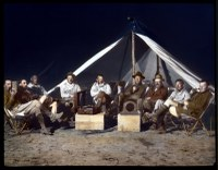 Circ. 1921-1930: Expedition group seated, enjoying Victrola, Third Asiatic Expedition, Gobi Desert, Mongolia.