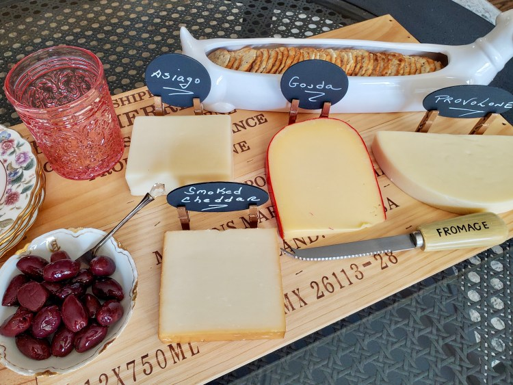 cheese markers, cheese, glasses, olives and crackers on the charcuterie board