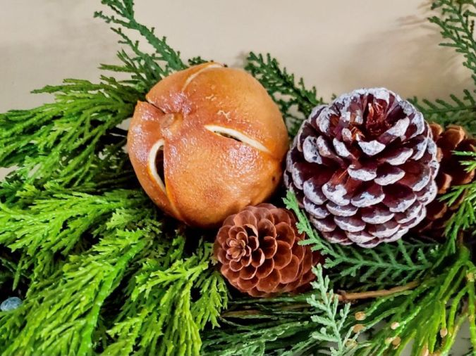 whole orange and pinecones on a portion of garland