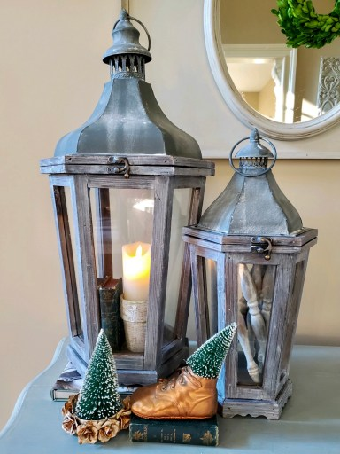 Large lantern filled with a battery operated candle sitting inside a flower pot.  Books are next to the flower pot.  The smaller lantern has spindles inside.  Baby shoe with a bottle brush tree inside.  A rose crown holds a bottle brush tree