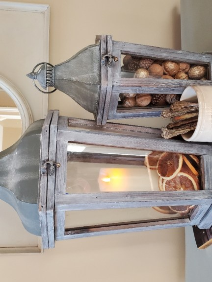 Two lanterns, one with a battery operated candle.  The other filled with nuts