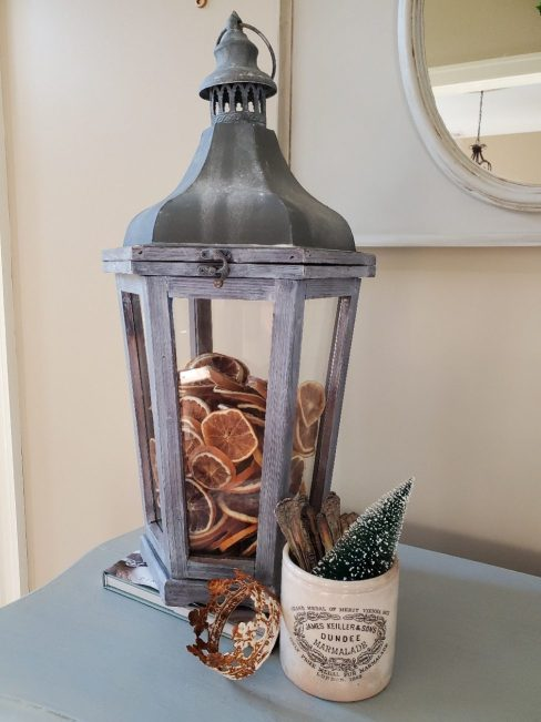 Large lantern on top of a book filled with dried orange slices.  White crock filled with silver and small bottle brush tree.  A crown is leaning
