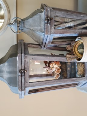 Lantern filled with small plates, stacked books and crewns.  Smaller lantern filled with spindles.  A white crock is filled with silver and a small picture