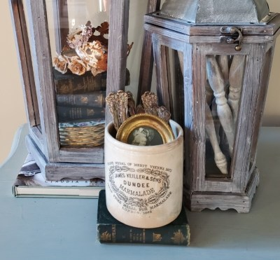 A close up of the spindles in the lantern and a close up of the white crock filled with silver and a picture