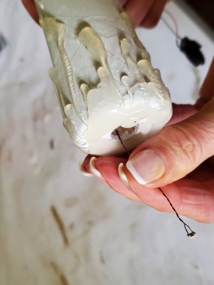 pulling the light bulb through the opening of the candle DIY