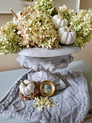 Urn filled with hydrangeas, small pumpkins