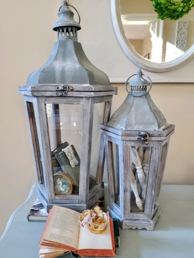 Larger lantern flled with leaning books and a lace bookmark and little picture.  The small lantern holds spindles.    A book is open with small crowns on top