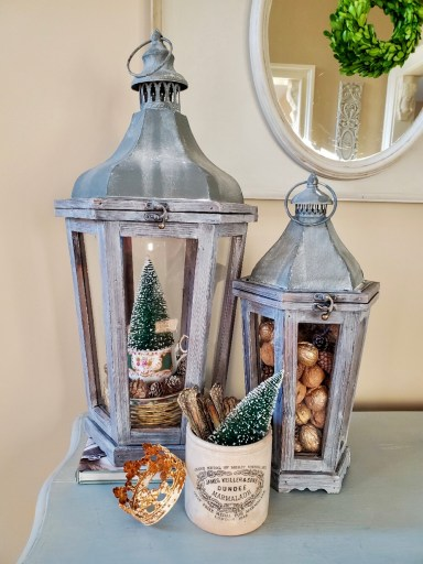 Large lantern filled with stacked dishes a tea cup sauce filled with small white tipped pinecones.  Then a tea cup with a bottle brush sitting inside.  Smaller lantern filled with walnut and pinecones.  White crock filled with silver and bottle brush tree with a crown leaning