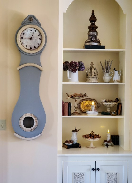 Showing the bookcase and the clock natrural fall decor