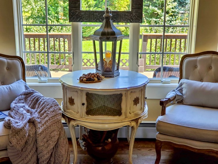 close up chairs by a window.   A heavy throw is on the chair arm.  A lantern with fall decor on a table with a tray
