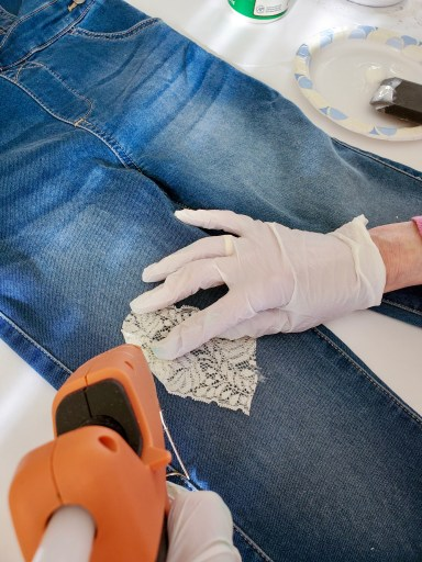 adding glue to lace as a patch on the leg of overalls for the DIY scarecrow