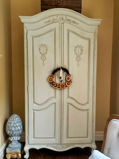 citrus wreath hanging showing the  full view of the French armoire