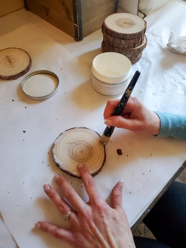 adding white wax to the edge of the top of the DIY wood coaster