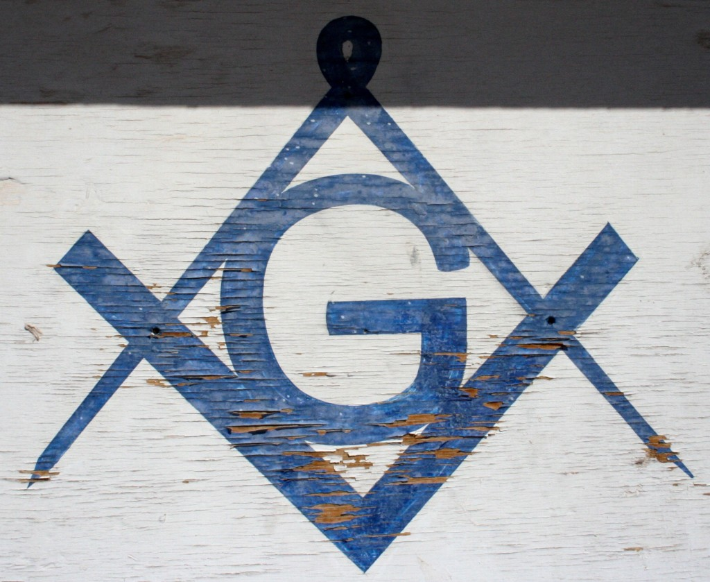 Freemason compass and square painted on temple door