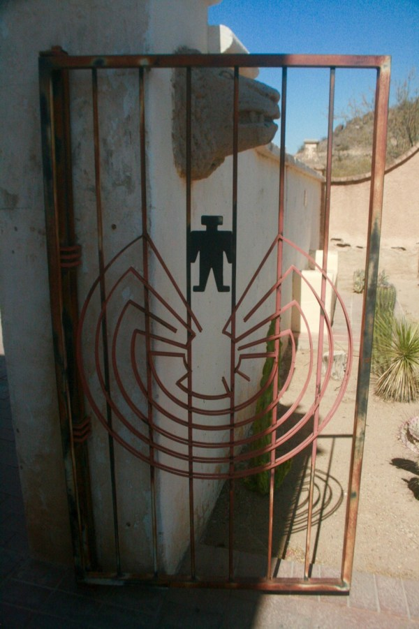 Tonto O'odham man in the maze symbol on a get next to solar lion head at San Xavier del bac Mission